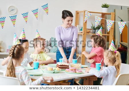 One of cute little boys telling joke to his friends and happy young female Stock photo © pressmaster