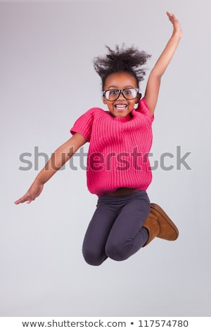 happy little african american girl jumping stock photo © dolgachov