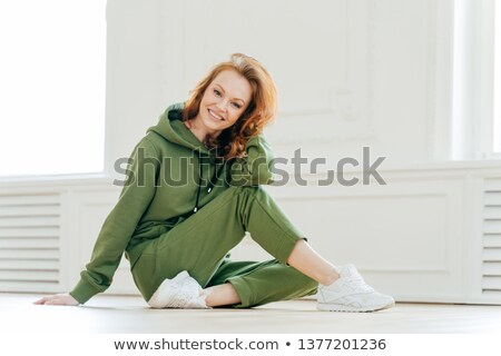 Delighted happy foxy woman busy with stretching pilate exercises in fitness studio, wears sportswear Stock photo © vkstudio