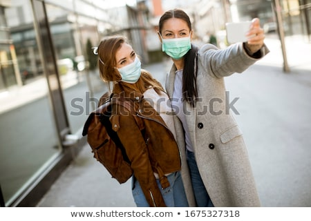 pretty young woman with protective facial mask on the street stock photo © boggy