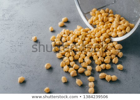 Dry clean chickpeas spilled on grey background from sieve. Food ingredients for vegetarians. Useful  Stock photo © vkstudio