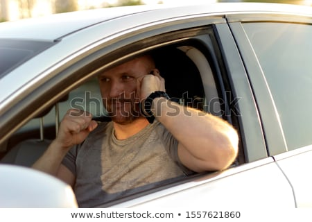 Image of bearded happy sportsman smiling while talking on smartp Stock photo © deandrobot