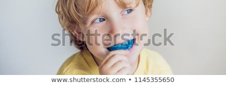 BANNER, LONG FORMAT Six-year old boy shows myofunctional trainer. Helps equalize the growing teeth a Stock photo © galitskaya