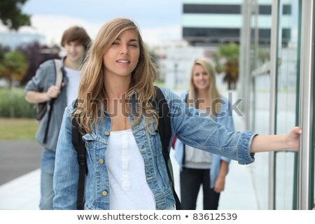 Three students walking on a campus, one of them about to open a door. Stock photo © photography33