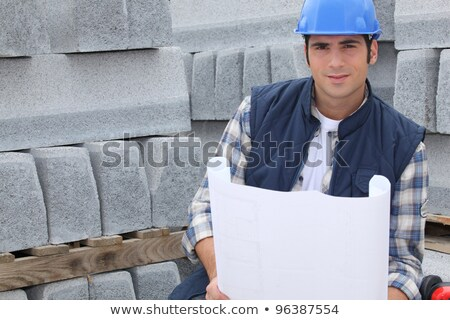 Construction worker standing next to pallets of concrete curb while looking at some plans Stock photo © photography33