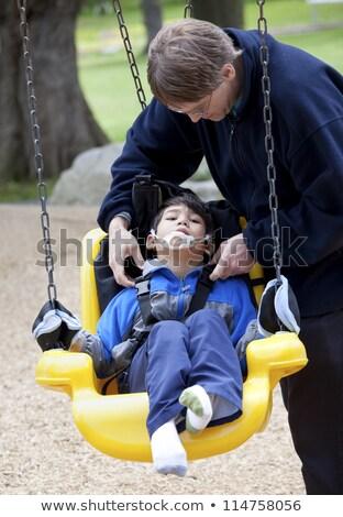 Ojciec popychanie niepełnosprawnych syn handicap huśtawka Zdjęcia stock © jarenwicklund