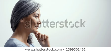 Grey-haired woman touching chin Stock photo © photography33