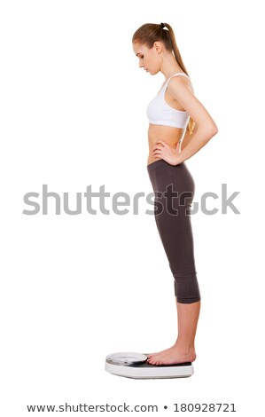 Young woman standing on a scale in a studio stock photo © wavebreak_media