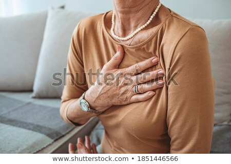 Female cardiologist touching with hand on chest Stock photo © stokkete