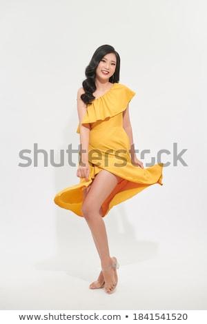 Fiatal nő citromsárga ruha ül pózol stúdió Stock fotó © maros_b