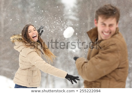 Happy excited young couple playing snowballs in winter forest Stock photo © deandrobot