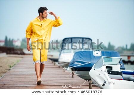Matróz férfi citromsárga köpeny sétál tenger Stock fotó © deandrobot