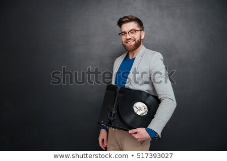 Portrait of cheerful bearded young man in glasses with turntable Stock photo © deandrobot