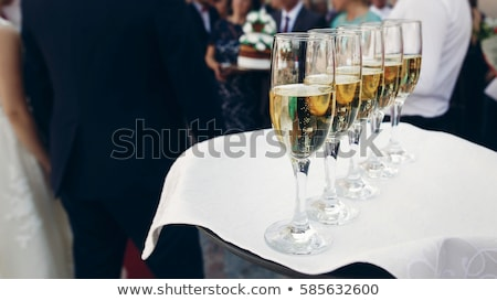 hand holds tray with yellow champagne glasses stock photo © denismart