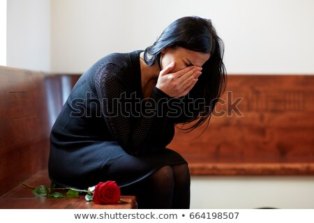 crying woman with red rose at funeral in church Stock photo © dolgachov