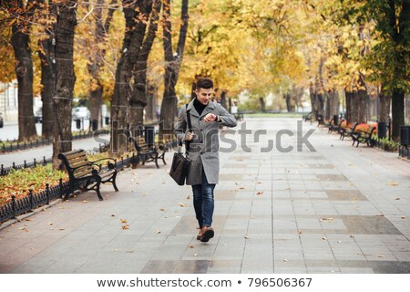 Picture of good-looking caucasian man in coat with bag strolling Stock photo © deandrobot