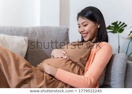 happy pregnant woman with headphones at home Stock photo © dolgachov
