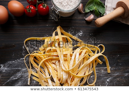 italian food background with pizza raw pasta and vegetables on wooden table stock photo © dash