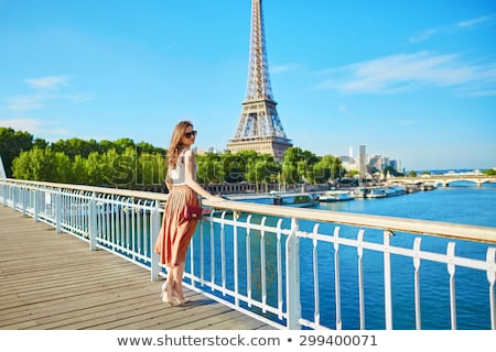 Beautiful young tourist girl near the Eiffel tower. stock photo © artfotodima