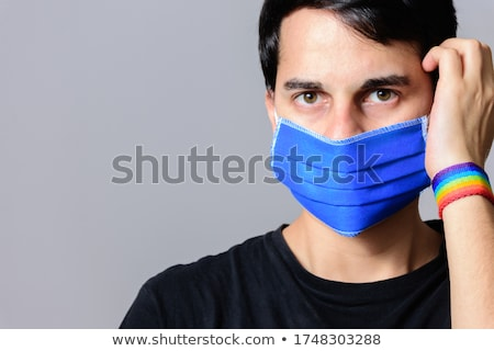 man with gay pride rainbow flag and wristband Stock photo © dolgachov