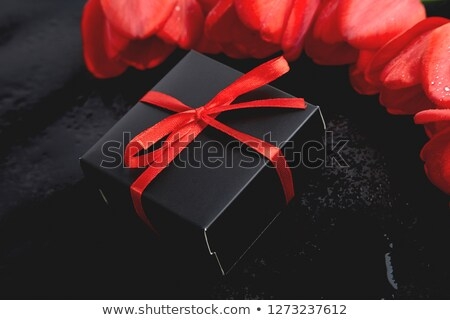 Black gift box with red ribbon near red tulip stock photo © Illia