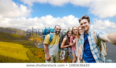 smiling woman with backpack over big sur hills Stock photo © dolgachov