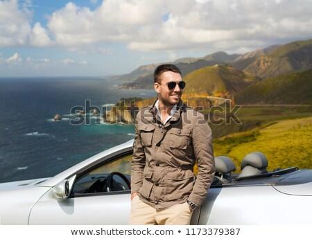 man at convertible car over big sur hills Stock photo © dolgachov