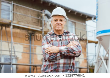 Stock photo: Proud plasterer standing in front of scaffold on construction site