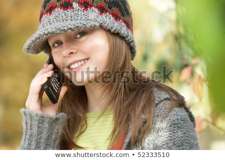 Head And Shoulders Of Young Girl In Autumn Woodland Using Mobile Stock photo © monkey_business