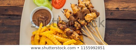Chicken satay served with peanut sauce and french fries Bali, Lifestyle BANNER, long format Stock photo © galitskaya