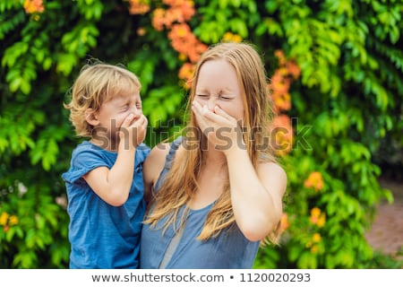 Mom and son sneeze in the park against the background of a flowering tree. Allergy to pollen concept Stock photo © galitskaya