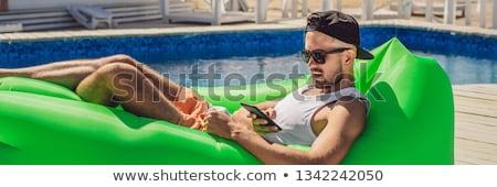 Jonge man genieten recreatie lucht sofa zwembad Stockfoto © galitskaya