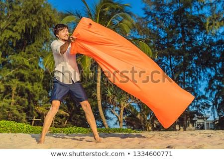 Summer lifestyle portrait of man inflates an inflatable orange sofa on the beach of tropical island. Stock photo © galitskaya