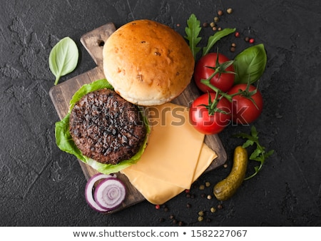 fresh grilled and raw minced pepper beef burger on vintage chopping board with buns onion and tomato stock photo © denismart