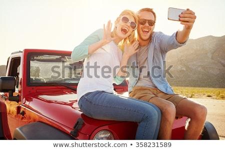 Stock photo: happy couple in car taking selfie by smartphone