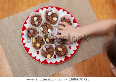 easter eggs in holders and candies on table Stock photo © dolgachov