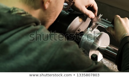 Workers measuring a metal workpiece Stock photo © Kzenon