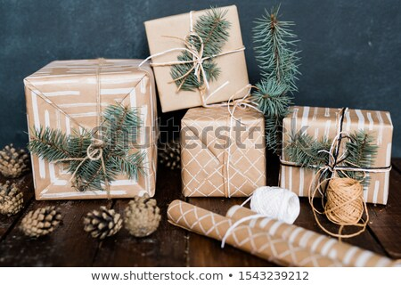 Giftboxes with conifer on top, rolled paper, threads for binding and pinecones Stock photo © pressmaster