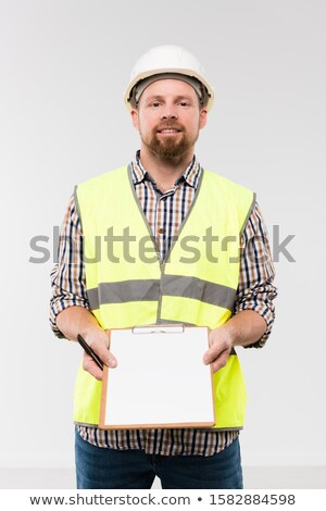 Cheerful young foreman showing clipboard with notes on paper in isolation Stock photo © pressmaster