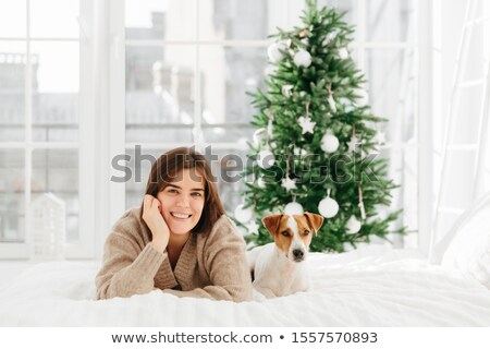 Relaxed beautiful dark haired young woman poses on bed with favourite pet, enjoys bedding time, has  Stock photo © vkstudio