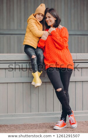 Vertical shot of pretty beautiful young woman dressed in red sweater and ragged jeans, stands closel Stock photo © vkstudio