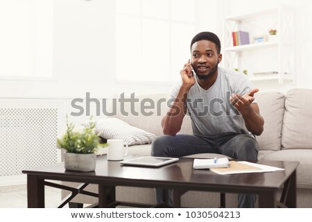 Image of african american man talking on smartphone at home Stock photo © deandrobot