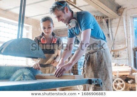 Team of carpenters working on the circular saw Stock photo © Kzenon