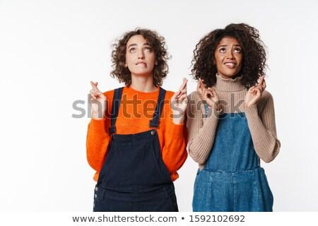 Portrait of multinational women looking upward with fingers crossed Stock photo © deandrobot