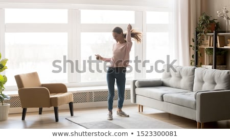 Fun teenage girl dancing with energy to music stock photo © darrinhenry