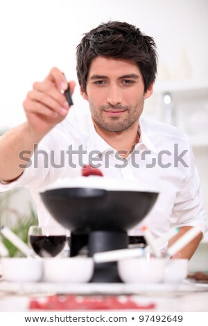 Man dipping raw beef into fondue Stock photo © photography33