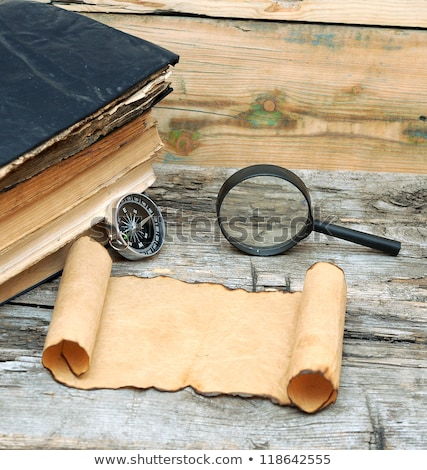 stack of antique books with compass magnifying glass and paper stock photo © inxti
