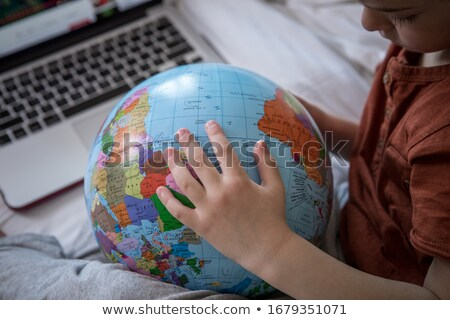 Student with laptop sitting on top of the earth globe Stock photo © Kirill_M