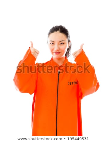 Young Asian woman showing thumb up sign with both hands in prisoners uniform Stock photo © bmonteny