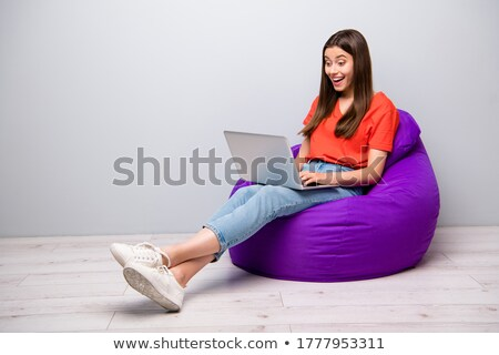 nice girl using laptop sitting in the room stock photo © deandrobot